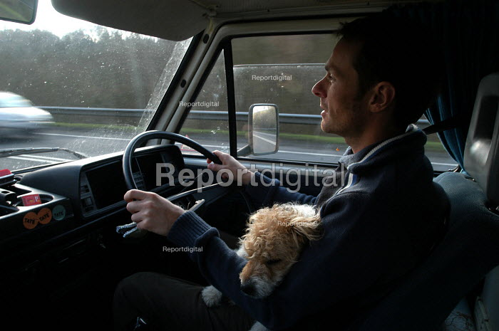 A man drives his camper van with his dog asleep on his lap - Paul Box - 2004-02-10