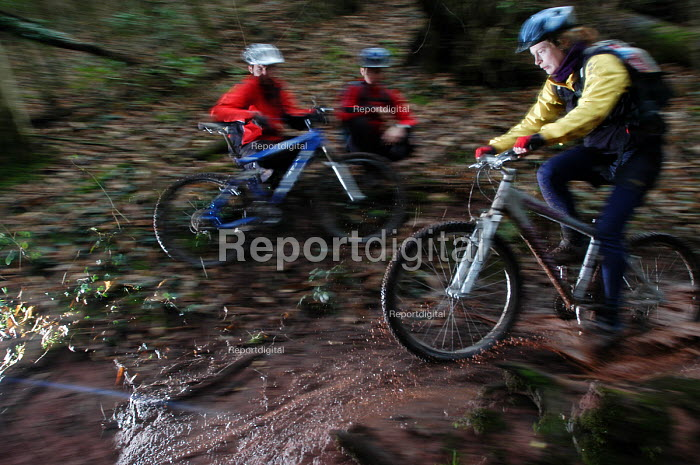 A mountain biker rides in the mud, watched by an instructor - Paul Box - 2004-02-02