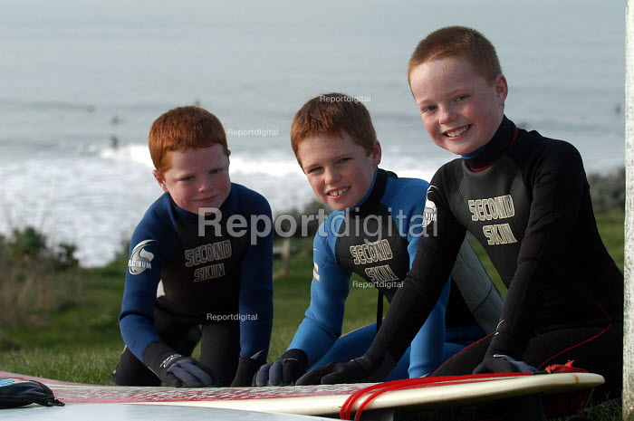 Ginger haired brothers wax surfboard before going surfing at Woolacombe in Devon - Paul Box - 2004-02-12