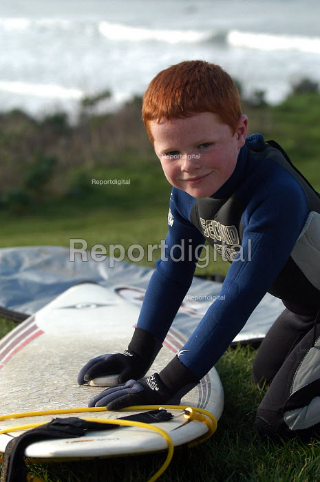 Ginger haired boy waxs surfboard before going surfing at Woolacombe in Devon - Paul Box - 2004-02-12