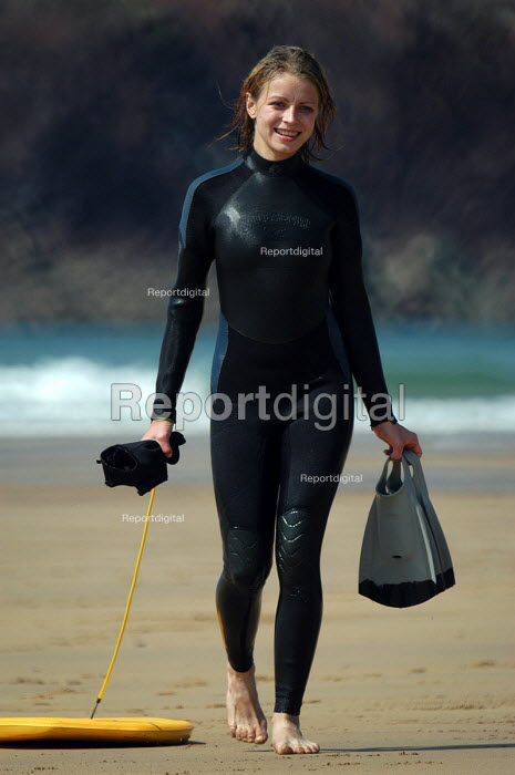 A woman in a wetsuit with bodyboard walks down the beach, Freshwater West, Pembrokeshire. - Paul Box - 2003-08-20