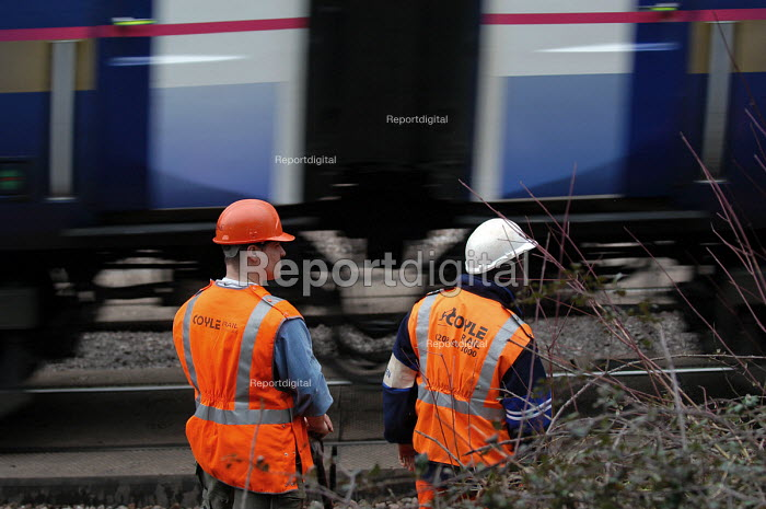 Railway engineers stand off to let train pass whilst working on railway lines near bristol - Paul Box - 2004-03-12