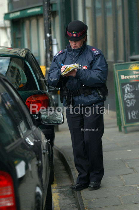 Woman parking attendant writing a parking ticket, Bristol - Paul Box - 2004-03-03