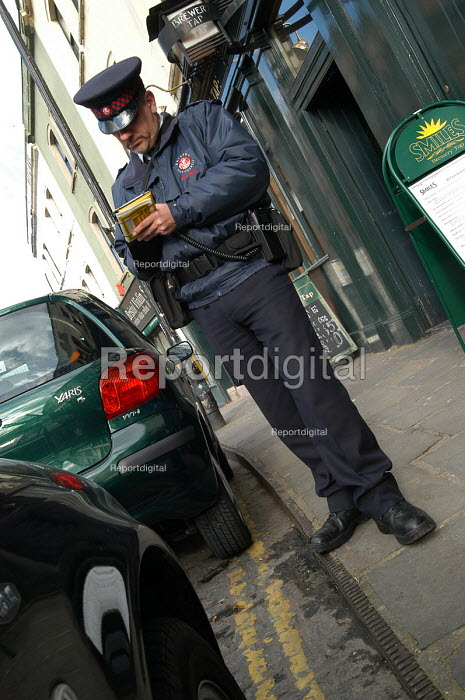 Parking attendant supervisor writes a parking ticket , Bristol - Paul Box - 2004-03-03