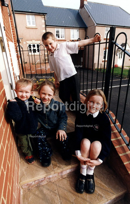 Social housing project near Taunton. Schoolchildren on front door steps of their home - Paul Box - 2003-08-01