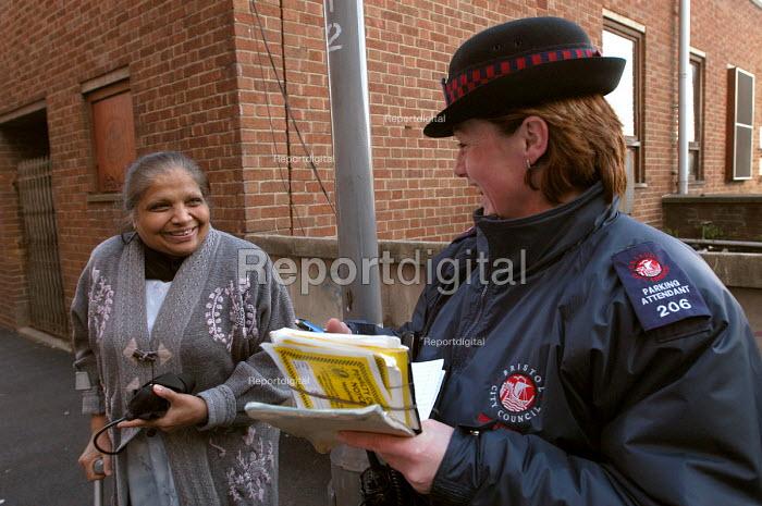 Woman parking attendant with an elderly asian woman, Bristol - Paul Box - 2004-03-03