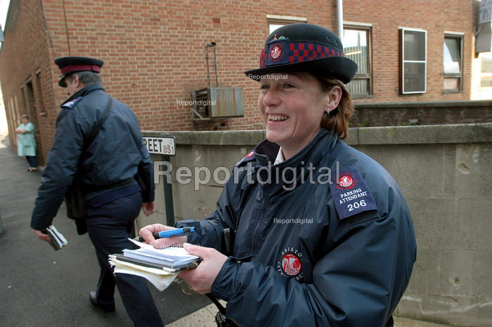 Woman parking attendant laughing with fellow worker, Bristol - Paul Box - 2004-03-03