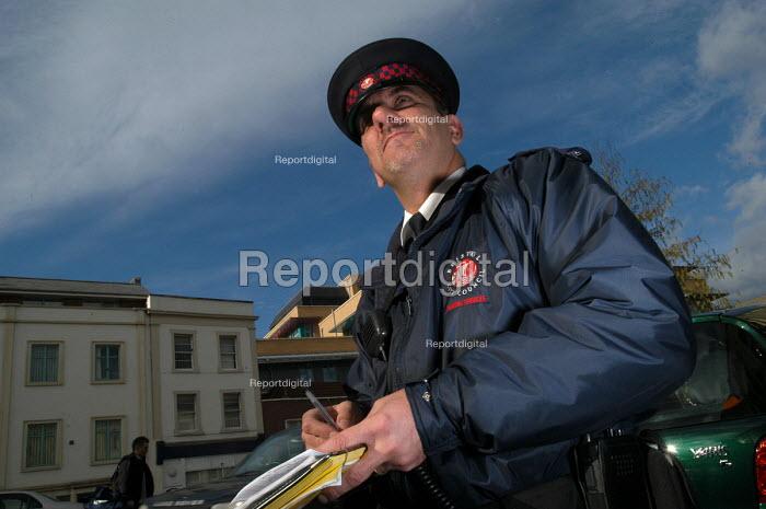 Parking attendant supervisor writes a parking ticket , Bristol - Paul Box - 2004-03-03