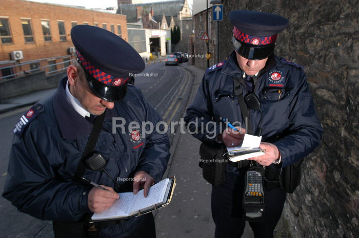 Parking attendant supervisor writes a parking ticket with newly trained attendant, Bristol - Paul Box - 2004-03-03
