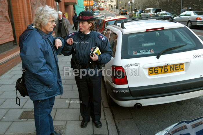 A woman parking attendant gives directions to an elderly lady, Bristol - Paul Box - 2004-03-03