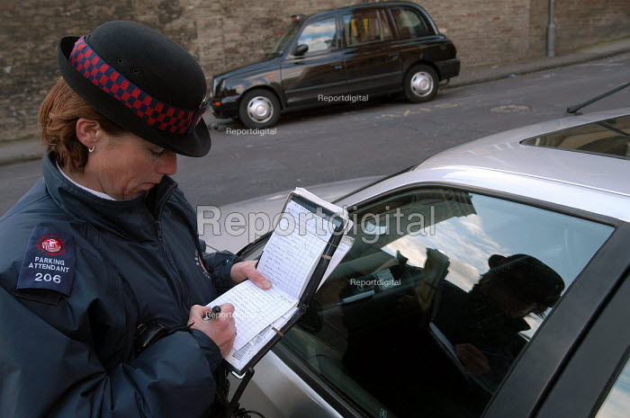 A female parking attendant , Bristol , gives a ticket. - Paul Box - 2004-03-03