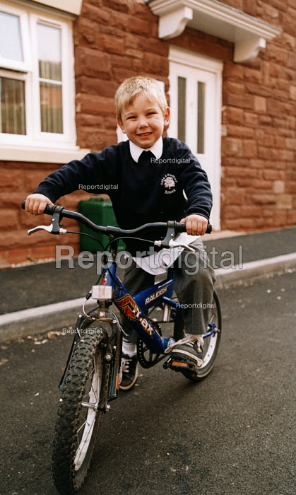 Social housing project near Taunton. Schoolboy on his bicycle in the street on their housing estate - Paul Box - 2003-08-01
