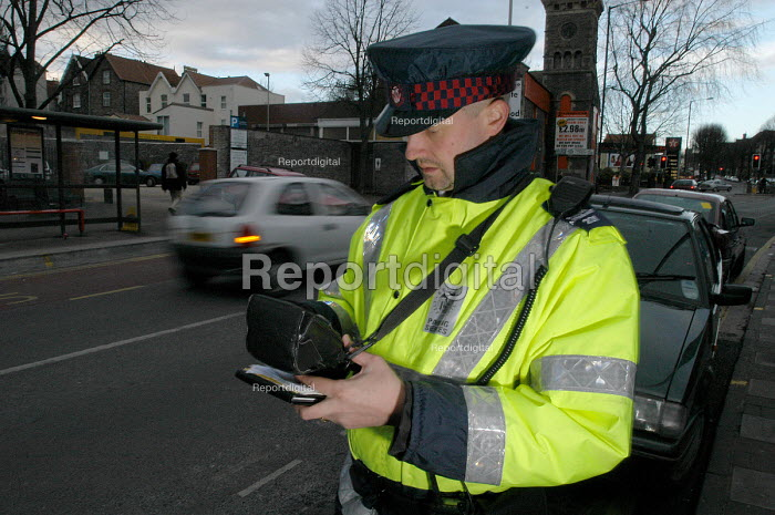 Parking attendant writes a parking ticket in a clearway zone for bus route, Bristol - Paul Box - 2004-03-03
