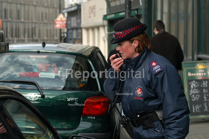 Woman parking attendant checking a road Tax disc, radioing into the control centre, Bristol - Paul Box - 2004-03-03