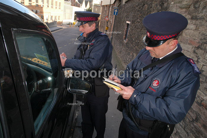 Parking attendant supervisor writes a parking ticket for a taxi with newly trained attendant, Bristol - Paul Box - 2004-03-03