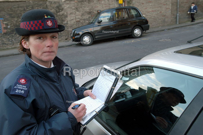A woman parking attendant, issuing a ticket. Bristol - Paul Box - 2004-03-03