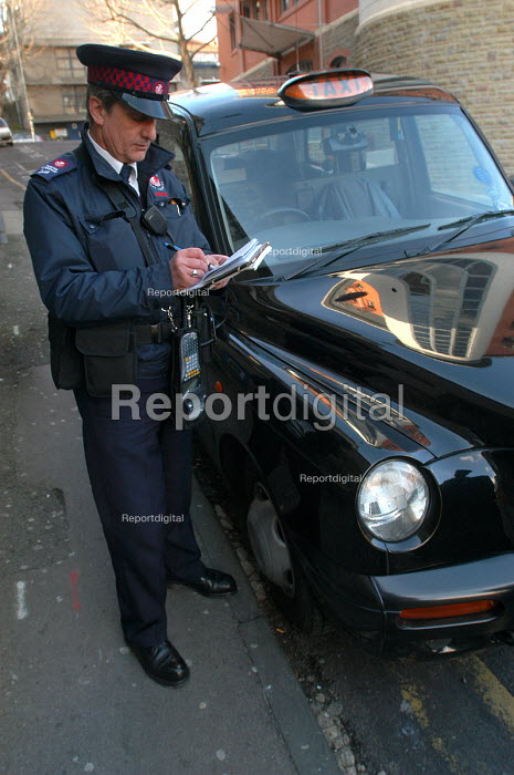 A newly trained parking attendant writes a parking ticket for a taxi , Bristol - Paul Box - 2004-03-03