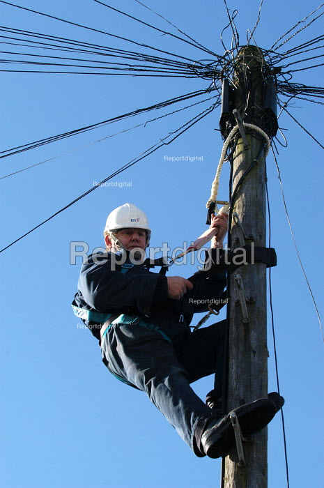 A British Telecom engineer works up telegraph pole - Paul Box - 2003-03-20