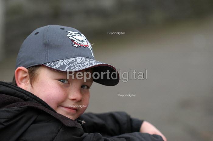 A boy sits on pavement wearing baseball cap - Paul Box - 2004-03-20