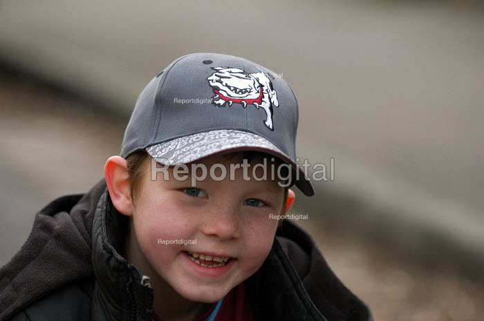 A boy sits on pavement wearing baseball cap - Paul Box - 2004-03-20