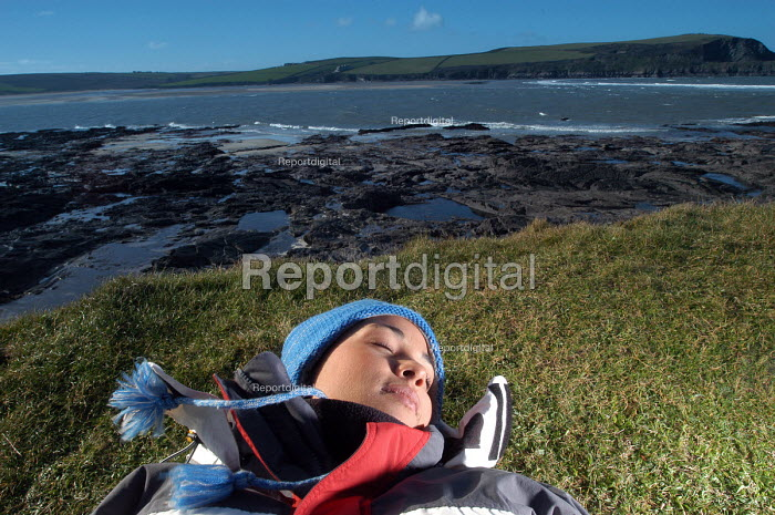 A young woman relaxes on a cliff overlooking the Camel estuary - Paul Box - 2004-02-10