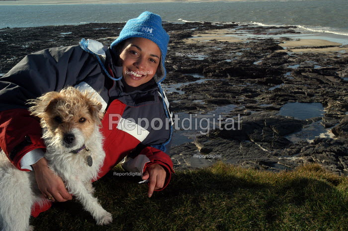 A young woman with her dog relaxes on a cliff overlooking the camel estuary - Paul Box - 2004-02-10