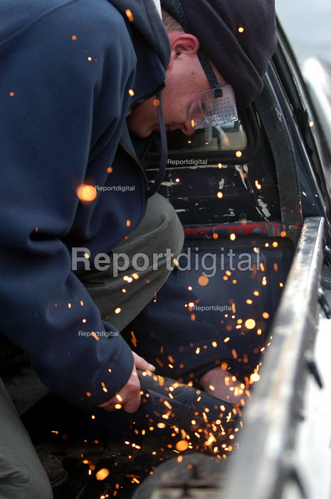 A Mechanic uses an angle grinder to repair a car at a garage. - Paul Box - 2004-02-10