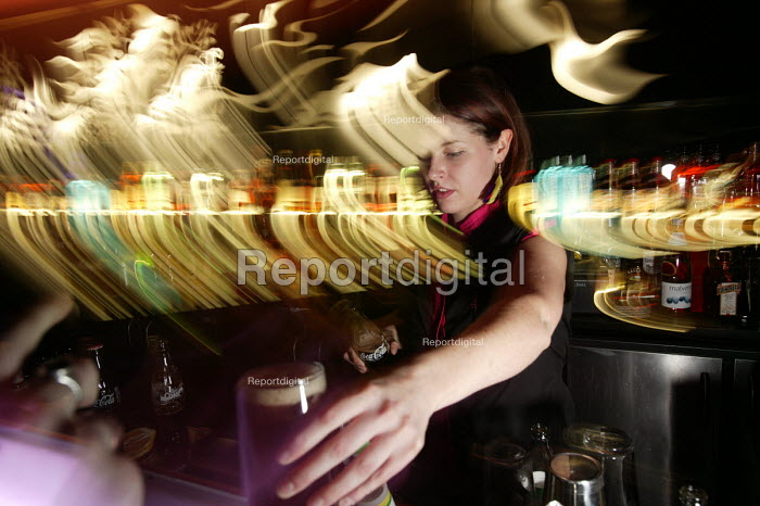 A female bar worker serves drinks at nightclub in Bristol - Paul Box - 2004-04-05