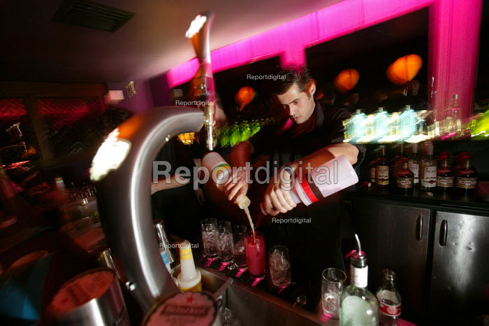 A male bar worker makes cocktails at a nightclub in Bristol - Paul Box - 2004-04-05