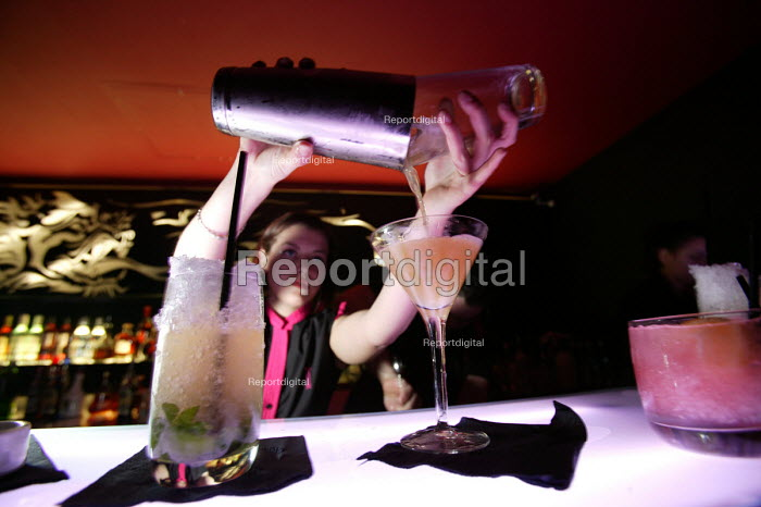 A female bar worker mixes cocktailss at nightclub in Bristol - Paul Box - 2004-04-05
