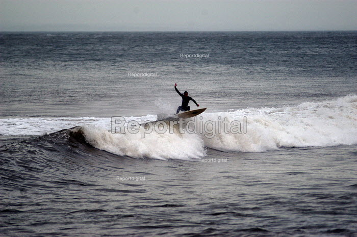 A surfer surfing, north coast of Devon in the winter - Paul Box - 2004-03-01