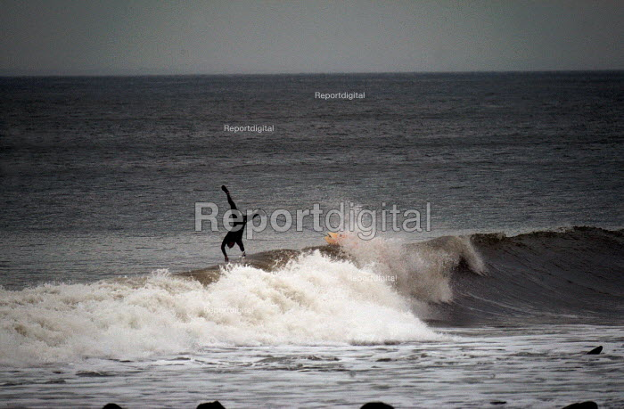 A surfer , surfing on the north coast of Devon in the winter. Jumps off weave to avoid rocks - Paul Box - 2004-03-01