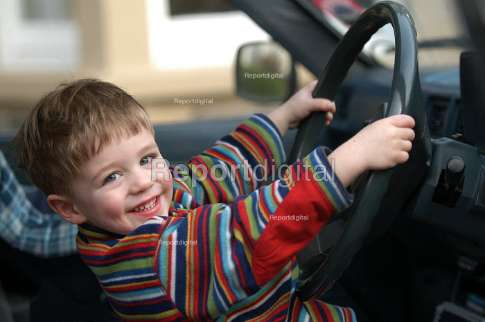 A young boy sits in the driving seat of dads car - Paul Box - 2004-03-20