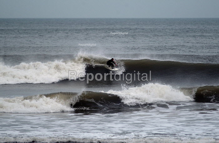 A surfer , surfing on the north coast of Devon in the winter. - Paul Box - 2004-03-01