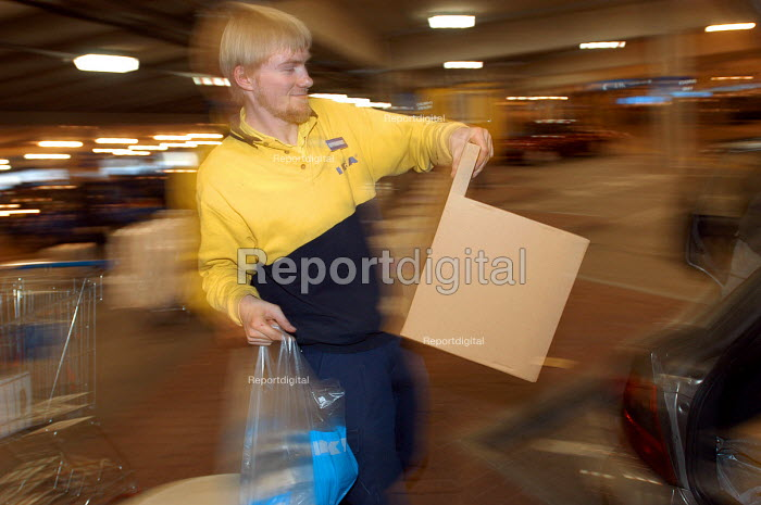 Ikea home furnishing store , loading area. An employee helps customers load their vehicles with flat pack items. - Paul Box - 2004-05-05