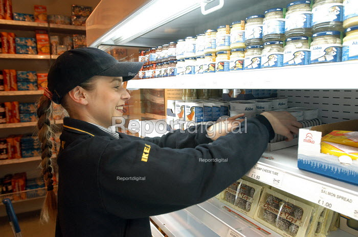 Ikea home furnishing store , a female employee stacks food in the chiller cabinet - Paul Box - 2004-05-05