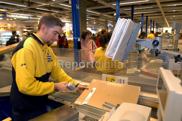 Ikea home furnishing store, a employee works at the check out - Paul Box - 2004-05-05
