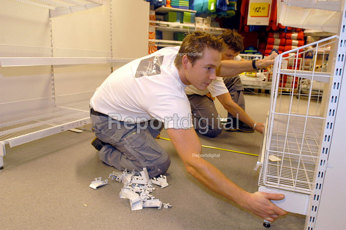 Ikea home furnishing store , an employee works putting together the store fittings - Paul Box - 2004-05-05