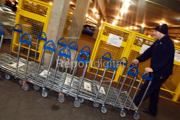 Ikea home furnishing store, loading area. An employee moves trollies. - Paul Box - 2004-05-05