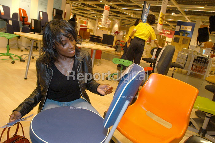 Ikea home furnishing store , customers shopping for home improvements. A woman looks at the price of furniture - Paul Box - 2004-05-05