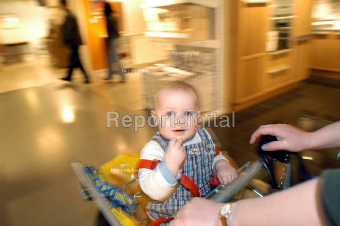 Ikea home furnishing store, customers shopping for home improvements. A baby sits in a trolley - Paul Box - 2004-05-05