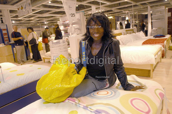 Ikea home furnishing store, customers shopping for home improvements. A woman sits on bed - Paul Box - 2004-05-05
