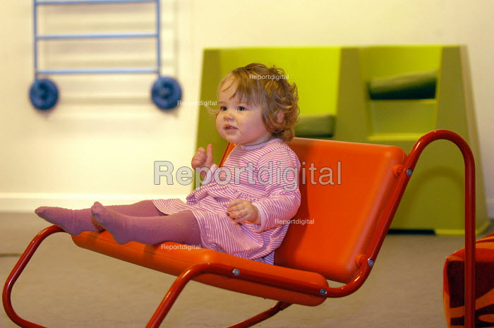 Ikea home furnishing store , a small child sits on an ikea chair - Paul Box - 2004-05-05