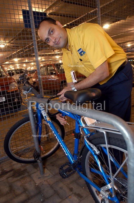 Ikea home furnishing store , a worker uses the companies cycles to get to work. pictured locking up his bike - Paul Box - 2004-05-05