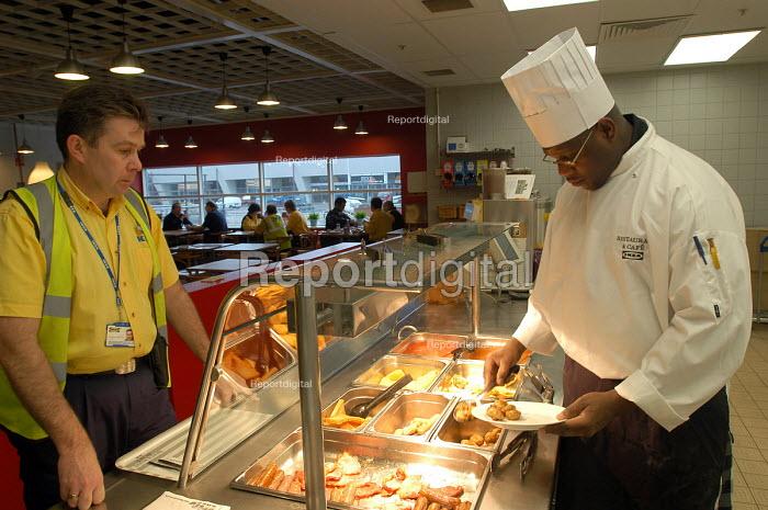 Ikea home furnishing store , a black chef prepares food for the ikea staff restaurant - Paul Box - 2004-05-05