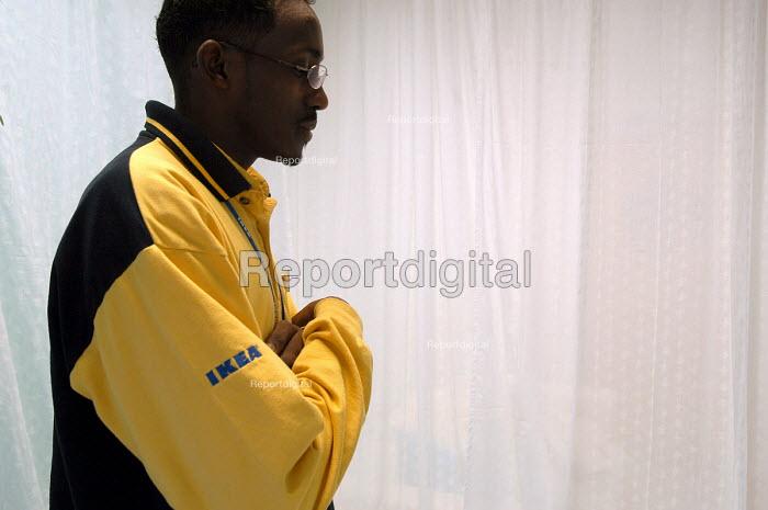 Ikea home furnishing store , a Muslim employee prays in the prayer room - Paul Box - 2004-05-05