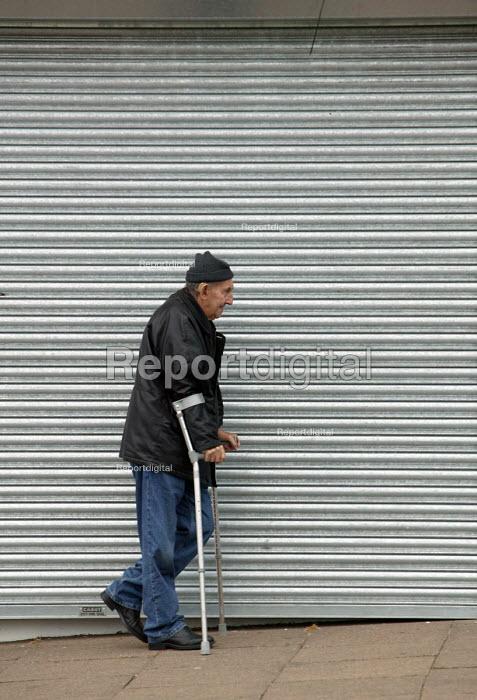 Disabled man walking down the street on crutches. Bristol - Paul Box - 2004-06-30