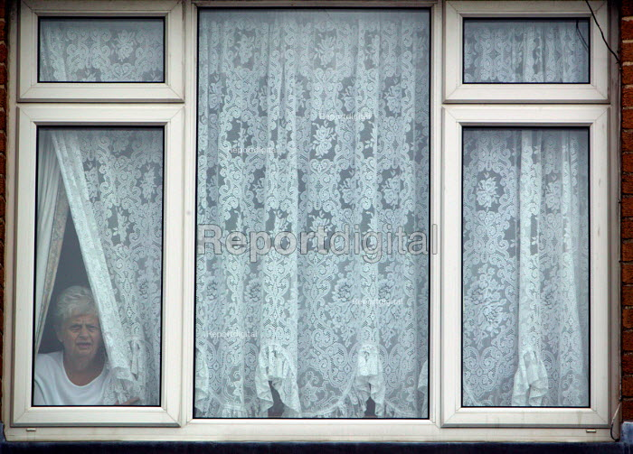 Resident looks out from behind the net curtains of her home, Lockleaze, Bristol where ASBO 's anti social behaviour orders have improved the area. - Paul Box - 2004-06-30