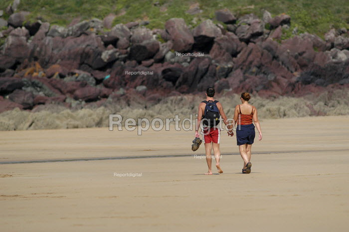 A couple walking down the beach on a hot day, Freshwater west, Pembrokeshire. - Paul Box - 2003-08-20