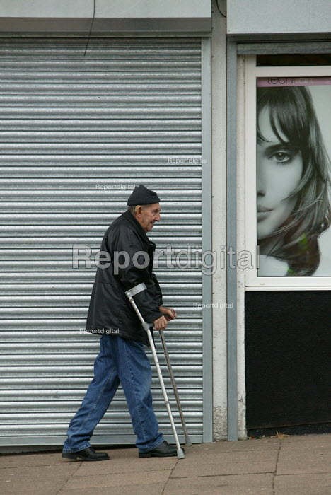Disabled man walking down the street on crutches past an advertisement for a hairdressers. Bristol - Paul Box - 2004-06-30